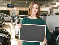 Smiling woman holding blackboard inside car dealership Stock Photos
