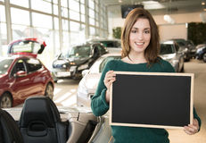 Smiling woman holding blackboard inside car dealership Stock Photo
