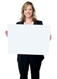 Smiling woman holding a blank billboard. Portrait of a happy young woman holding a blank billboard over white background Royalty Free Stock Photography