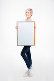 Smiling woman holding blank board. Full length portrait of a smiling cute woman holding blank board  on a white background Stock Photography