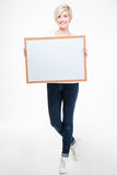 Smiling woman holding blank board. Full length portrait of a smiling woman holding blank board  on a white background Stock Photo