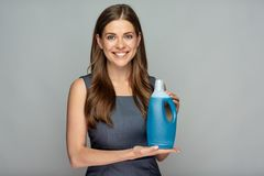 Smiling woman holding blue cleaner bottle. Stock Image