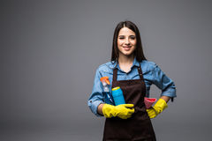 Smiling woman holding bottle of chemistry for cleaning house. Isolated portrait. Royalty Free Stock Photos