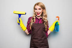 Smiling woman holding bottle of chemistry for cleaning house. Royalty Free Stock Photography