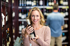 Smiling woman holding bottle of wine Stock Photo