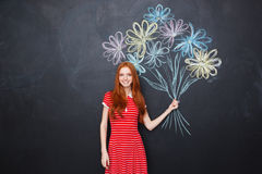 Smiling woman holding bouquet of drawn flowers over blackboard background Royalty Free Stock Image