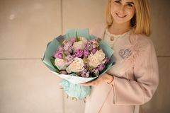 Smiling woman holding a bouquet of tender bright violet and peach color flowers. Wrapped in the blue paper royalty free stock photos