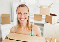 Smiling woman holding boxes after moving Stock Image