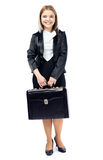 Smiling woman holding briefcase looking at camera Royalty Free Stock Image
