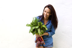 Smiling woman holding bunch of vegetables Royalty Free Stock Photos