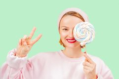 Smiling woman is holding candy lollipop  on pastel green background stock photo
