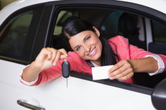 Smiling woman holding car key and business card. At new car showroom Stock Image