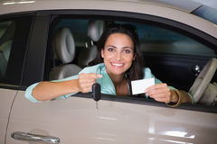 Smiling woman holding car key and business card Stock Image