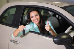 Smiling woman holding car key while giving thumbs up. At new car showroom Stock Photography