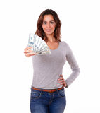 Smiling woman holding cash dollars while standing Stock Images