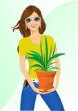 Smiling woman holding chlorophytum Royalty Free Stock Photo