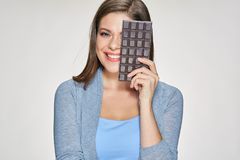 Smiling woman holding chocolate bar. Isolated portrait of young woman with sweets Stock Photos