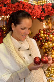 Smiling woman holding Christmas balls at shop Royalty Free Stock Photo