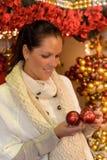 Smiling woman holding Christmas balls at shop Royalty Free Stock Photo