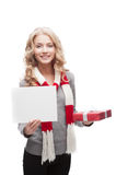 Smiling woman holding christmas gift and sign Royalty Free Stock Photos