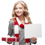 Smiling woman holding christmas gift and sign Royalty Free Stock Image
