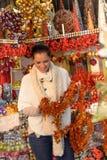 Smiling woman holding Christmas tinsel at shop Royalty Free Stock Photo
