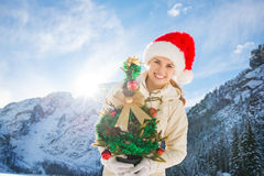 Smiling woman holding Christmas tree in the front of a mountains Royalty Free Stock Photography