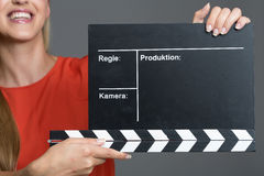 Smiling woman holding a clapperboard Royalty Free Stock Image