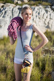 Smiling woman holding climbing equipment Stock Photo