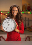 Smiling woman holding clock in christmas decorated kitchen Royalty Free Stock Photos