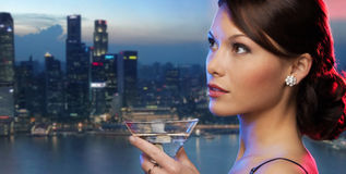 Smiling woman holding cocktail over night city Stock Photo