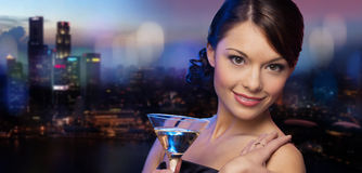 Smiling woman holding cocktail over night city Royalty Free Stock Images