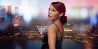 Smiling woman holding cocktail over night city Stock Image