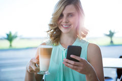 Smiling woman holding a coffee glass and using her mobile phone Royalty Free Stock Photo