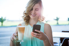 Smiling woman holding a coffee glass and using her mobile phone Stock Photography