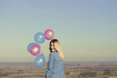 Smiling woman holding colorful balloons. In the field Stock Image