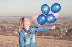 Smiling woman holding colorful balloons. In the field Royalty Free Stock Images