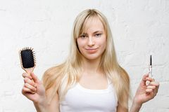 Smiling woman holding comb and scissors Stock Images