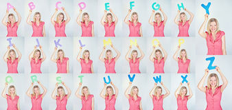 Smiling woman holding complet alphabet letters Stock Photos