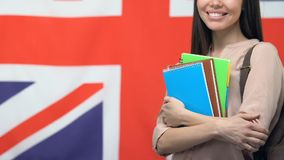 Smiling woman holding copybooks, standing against UK flag, education in Britain. Stock footage stock footage