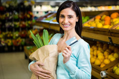 Smiling woman holding credit card and grocery bag Stock Photography
