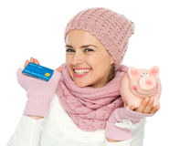 Smiling woman holding credit card and piggy bank Stock Photo