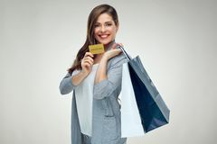 Smiling woman holding credit card with shopping bag. With purchases Royalty Free Stock Photos