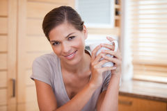 Smiling woman holding a cup in the kitchen stock photo
