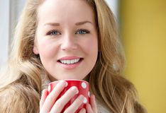Smiling woman holding cup of tea Stock Image