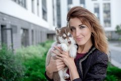 Smiling woman holding cute husky puppy stock photography