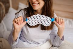 Smiling woman holding a cute sleep mask with the geometric print. Young smiling woman holding a cute sleep mask with the geometric print on the background of a stock images