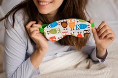 Smiling woman holding a cute sleep mask with the owl print. Young smiling woman holding a cute sleep mask with the owl print on the background of a white bed stock photo