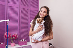 Smiling woman holding cute wet yorkshire terrier dog wrapped in towel after bath. Beautiful smiling woman holding cute wet yorkshire terrier dog wrapped in towel Royalty Free Stock Images