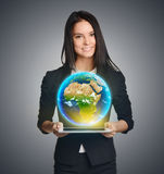 Smiling woman holding Earth globe over tablet Stock Image